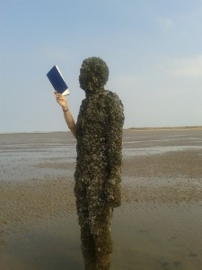 Be-barnacled Antony Gormley statue reading on Crosby beach.