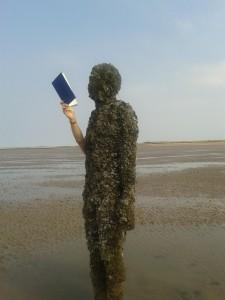 Be-barnacled Antony Gormley statue reading on Crosby beach.